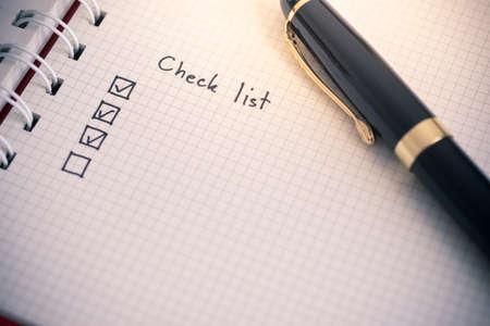 Photo pour Check list writing on business notebook paper - image libre de droit