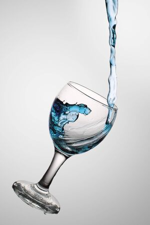 Dark blue water flows in a wine-glass. In a glass from glass a wave