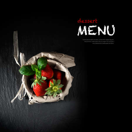 Photo for Creatively lit concept image for a dessert menu blackboard. Fresh strawberries and mint leaves in a brown paper bag. Copy space. - Royalty Free Image