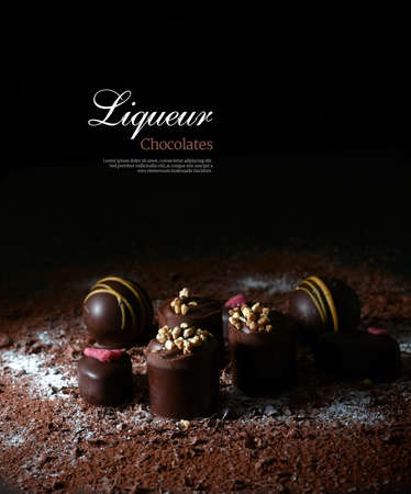 Photo for Creatively lit dark liqueur chocolates against a dark background. Copy space. - Royalty Free Image