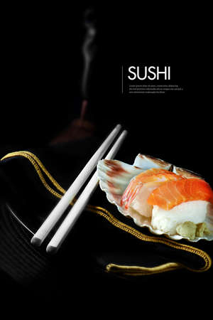 Photo pour Fresh Japanese sushi with chop sticks, burning incense and luxury napkin against a black background. Generous accommodation for copy space. - image libre de droit