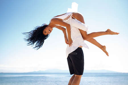 Photo pour Happy couple, man raised his girlfriend on the his shoulder, isolated on a sunny sky, beach, blue water. Vacantion in Greece. - image libre de droit
