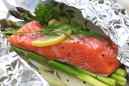 Foto de fresh salmon with asparagus in foil paper ready for cooking - Imagen libre de derechos