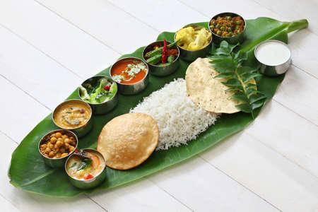 Foto de meals served on banana leaf, traditional south indian cuisine - Imagen libre de derechos