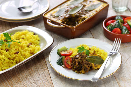 Foto de bobotie and yellow rice, south african cuisine. bobotie is a curry flavored meatloaf with baked egg on top. - Imagen libre de derechos