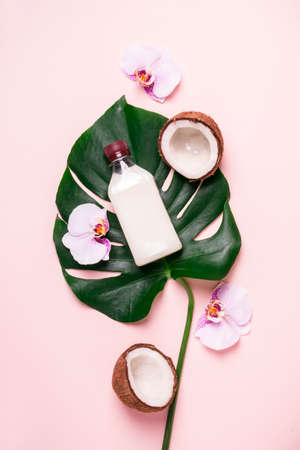 Photo for Coconut oil and tropical leaves and flowers. Hair care spa concept. - Royalty Free Image