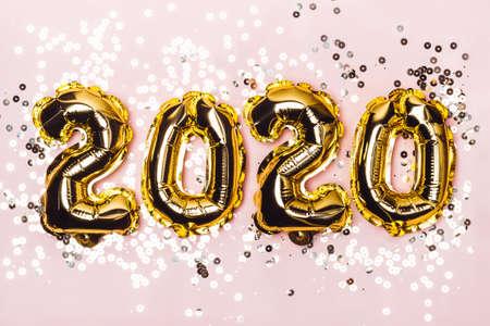 Foto de Golden foil balloons 2020 and sparkles on pink pastel - Imagen libre de derechos