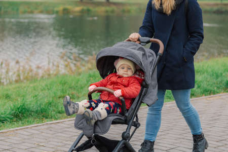Photo pour A woman walks in the park with a stroller and a small child near the lake. - image libre de droit