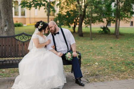 Foto de Newlyweds sit on a bench in the park. - Imagen libre de derechos
