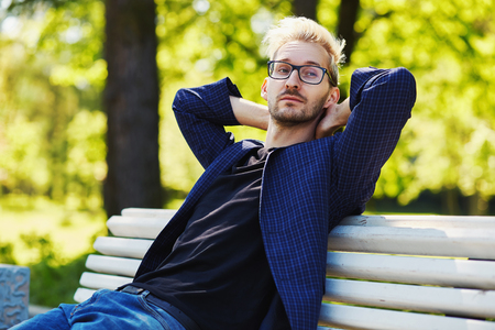 Photo for Blond male in glasses and dark jacket sitting on white park bench leaning on back with hands behind head and looking away on blurred background on sunny day - Royalty Free Image