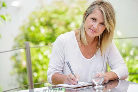 Foto de middle aged blond woman working at home without stress - Imagen libre de derechos