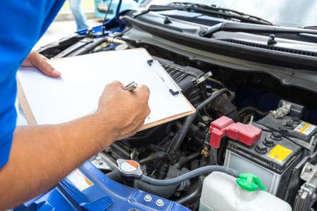 Photo pour Mechanic man holding clipboard and check the car - image libre de droit