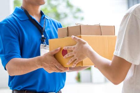 Photo pour Woman hand accepting a delivery of boxes from deliveryman - image libre de droit