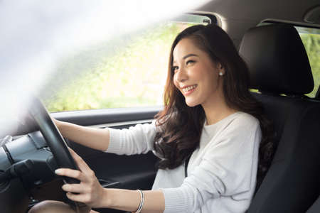 Foto de Asian women driving a car and smile happily with glad positive expression during the drive to travel journey, People enjoy laughing transport and relaxed happy woman on roadtrip vacation concept - Imagen libre de derechos