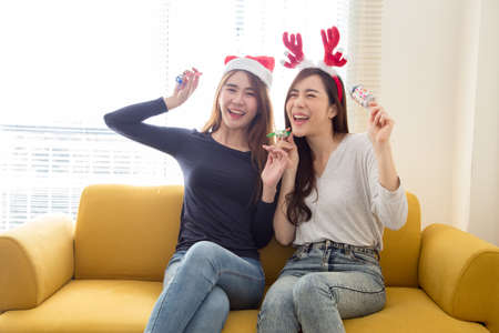 Photo pour Happy friends two young asian woman laughing and having fun together with celebrating christmas or new year or birthday party on yellow sofa in the living room at home, Crazy day with friend concept - image libre de droit