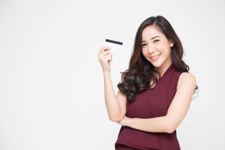 Photo pour Young beautiful Asian woman smiling, showing, presenting credit card for making payment or paying online business, Pay a merchant or as a cash advance for goods, Cardholder or A person who owns a card - image libre de droit