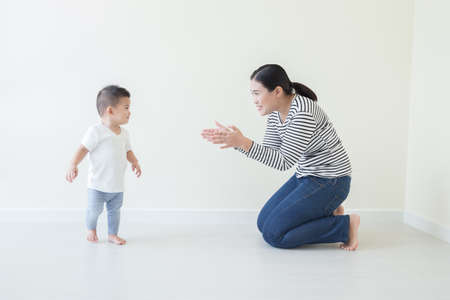 Photo pour Asian baby boy learning to walk with watching and take care by mom, Son take first steps at home - image libre de droit