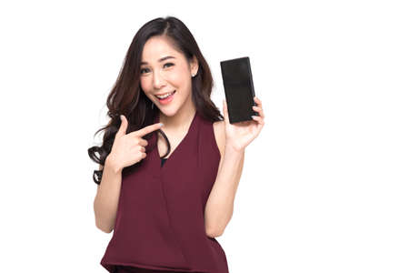 Photo pour Portrait of a cheerful beautiful girl wearing red dress and showing or presenting mobile phone application and pointing finger to smartphone on hand isolated over white background, Asian Thai model - image libre de droit