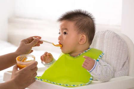 Foto de Mom is feeding liquid food to her Asian son - Imagen libre de derechos