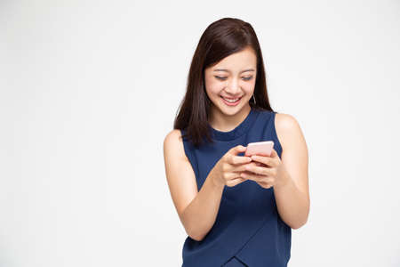 Foto de Cheerful young Asian woman using smartphone and receiving good news from the message on mobile chat application over white background - Imagen libre de derechos