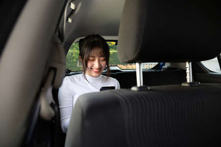 Photo pour Asian teenager woman using a smartphone in back seat of car, Passengers use an app to order a ride and Peer-to-peer ride sharing concept - image libre de droit