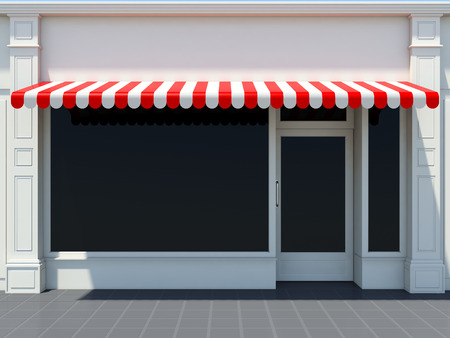 Foto de White shopfront in the sun - classic store front with red awnings - Imagen libre de derechos