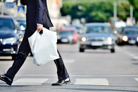 Photo for Man in suit with plastic bag crossing street - Royalty Free Image