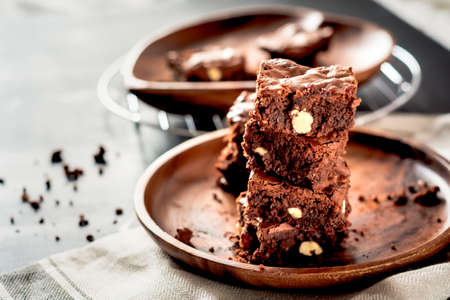 Foto de Piece of stack homemade dark chocolate brownies topping with almond slices and mint on wood table with copy space. - Imagen libre de derechos