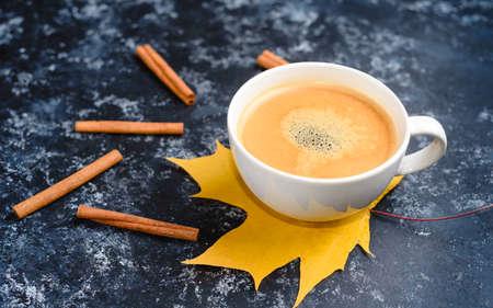 Foto de Autumn coffee composition, coffee cup with foam, cinnamon, autumn leaf at black background. - Imagen libre de derechos
