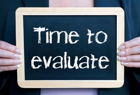 Foto de woman holding chalkboard with Time to evaluate  - Imagen libre de derechos