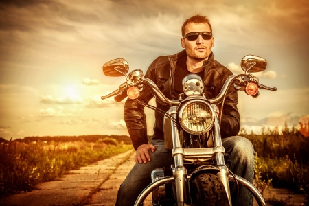 Biker man wearing a leather jacket and sunglasses sitting on his motorcycle looking at the sunset