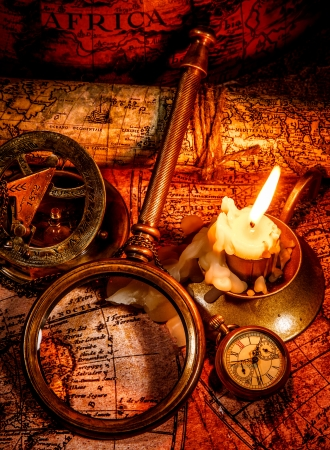 Photo pour Vintage compass, magnifying glass, pocket watch, spyglass lie on an old ancient map with a lit candle  Vintage still life  - image libre de droit