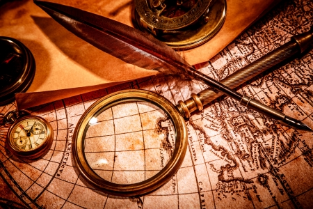 Photo pour Vintage magnifying glass, compass, goose quill pen, spyglass and a pocket watch lying on an old map. - image libre de droit