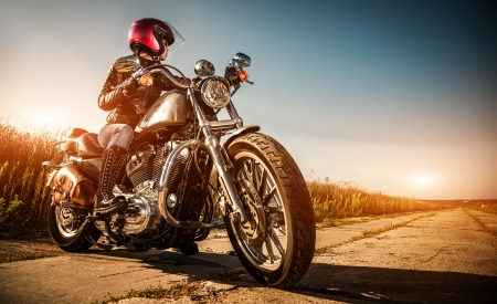 Biker girl on a motorcycle in a leather jacket and a helmet, looks at the way
