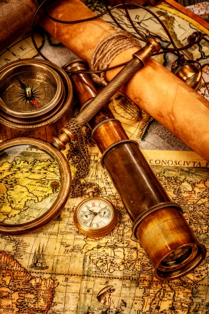 Photo pour Vintage magnifying glass, compass, telescope and a pocket watch lying on an old map. - image libre de droit