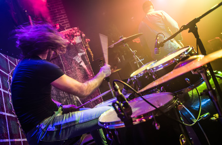 Photo for Drummer (blurred motion) playing on drum set on stage. Focus on the drum and microphone. - Royalty Free Image