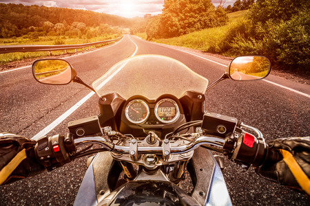 Photo for Biker driving a motorcycle rides along the asphalt road. First-person view. - Royalty Free Image