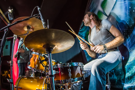 Photo for Drummer (focus on the drum and microphone) playing on drum set on stage. - Royalty Free Image