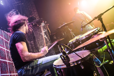 Photo for Drummer playing on drum set on stage. Warning - Focus on the drum, authentic shooting with high iso in challenging lighting conditions. A little bit grain and blurred motion effects. - Royalty Free Image