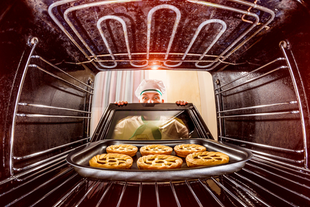 Photo pour Chef prepares pastries in the oven, view from the inside of the oven. Cooking in the oven. - image libre de droit