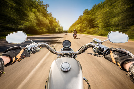 Foto de Biker driving a motorcycle rides along the asphalt road. First-person view. - Imagen libre de derechos