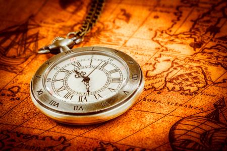 Foto de Vintage Antique pocket watch on an ancient world map in 1565.. - Imagen libre de derechos