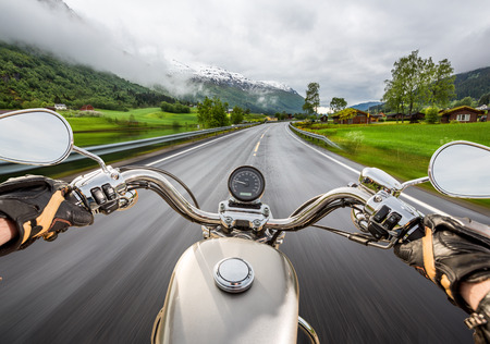 Biker girl rides a motorcycle in the rain. First-person view.