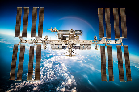 International Space Station over the planet earth. Elements of this image furnished by NASA.
