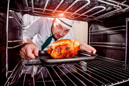 Photo pour Chef prepares roast chicken (focus on chicken) in the oven, view from the inside of the oven. Cooking in the oven.Thanksgiving Day. - image libre de droit