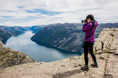 Photo pour Nature photographer tourist with camera shoots while standing on top of the mountain. Beautiful Nature Norway Preikestolen or Prekestolen. - image libre de droit