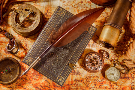 Photo for Vintage still life - magnifying glass, pocket watch, old book and goose quill pen lying on an old map in 1565. - Royalty Free Image
