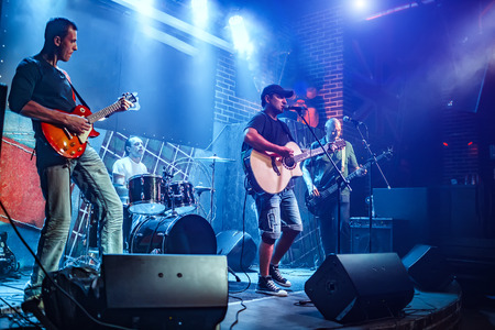 Photo for Band performs on stage, rock music concert. Warning - authentic shooting with high iso in challenging lighting conditions. A little bit grain and blurred motion effects. - Royalty Free Image