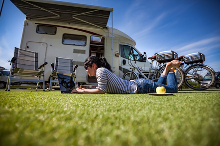 Foto de Woman on the grass, looking at the laptop near the ?amping. Caravan car Vacation. Family vacation travel, holiday trip in motorhome - Imagen libre de derechos