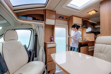 Photo pour Woman in the interior of a camper RV motorhome with a cup of coffee looking at nature. - image libre de droit
